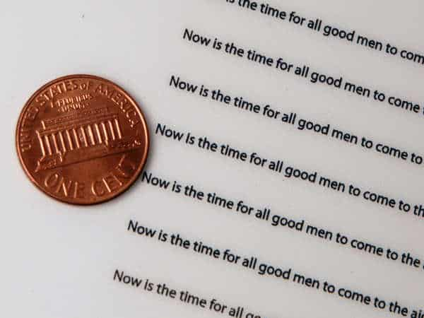 Small extremely clear sentences made through UV Curing Printing with a penny for scale.