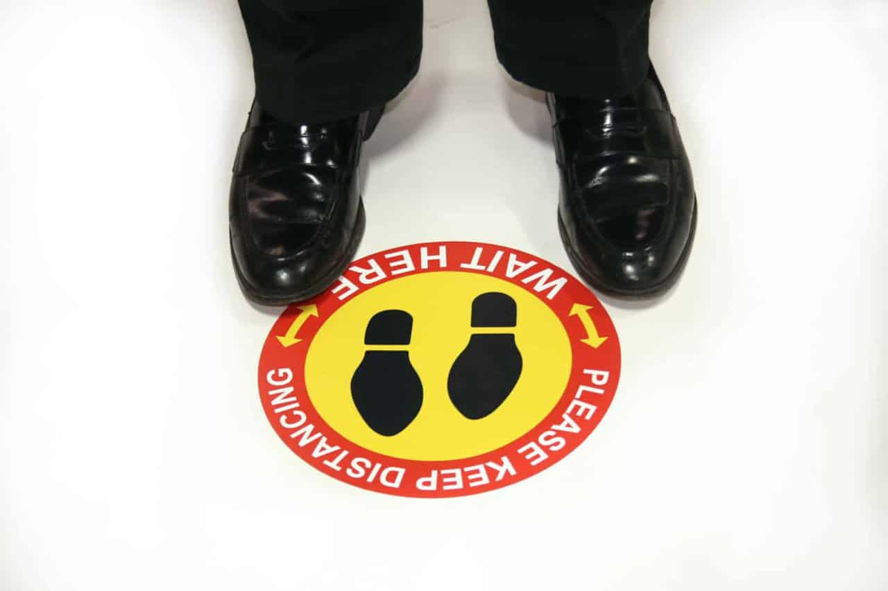 Man in dress shoes standing at a social distancing graphic