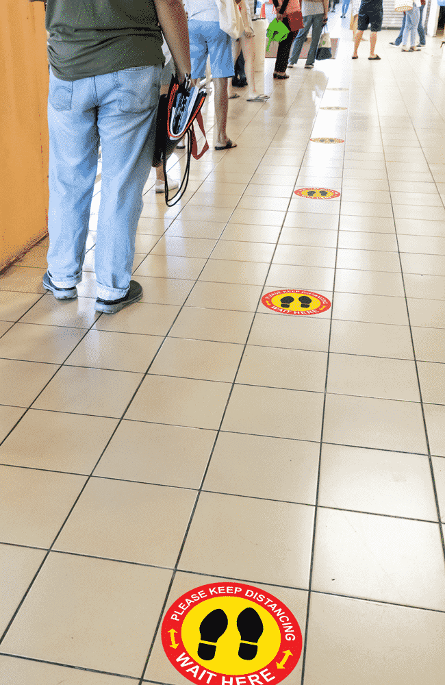 Individuals in line spaced out with social distancing stickers